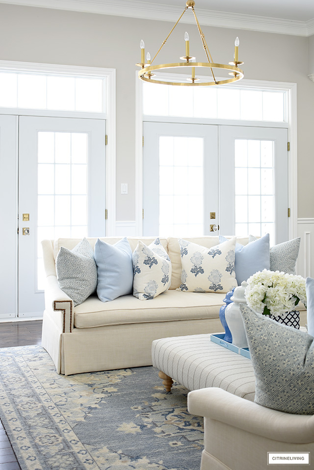 A gorgeous spring decorated living room with elegant soft blue and white throw pillows and a soft blue and beige rug.