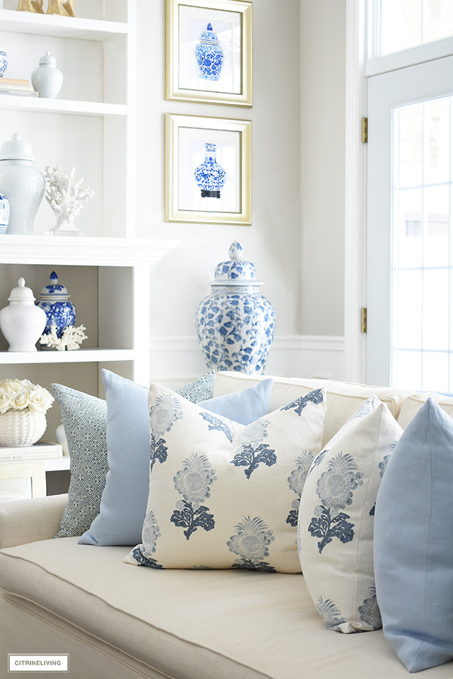 Spring living room decor with gorgeous throw pillows in soft blue and white floral and geometric prints, chinoiserie art prints and ginger jars.