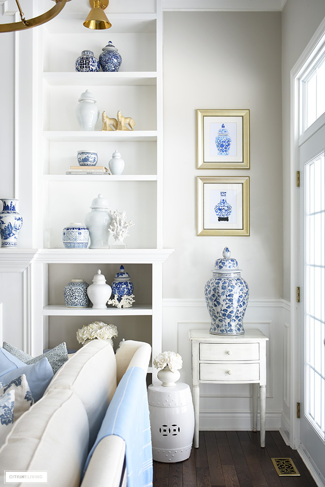 Spring living rom decor with styled bookshelves in blue and white ginger jars and coral sculptures.