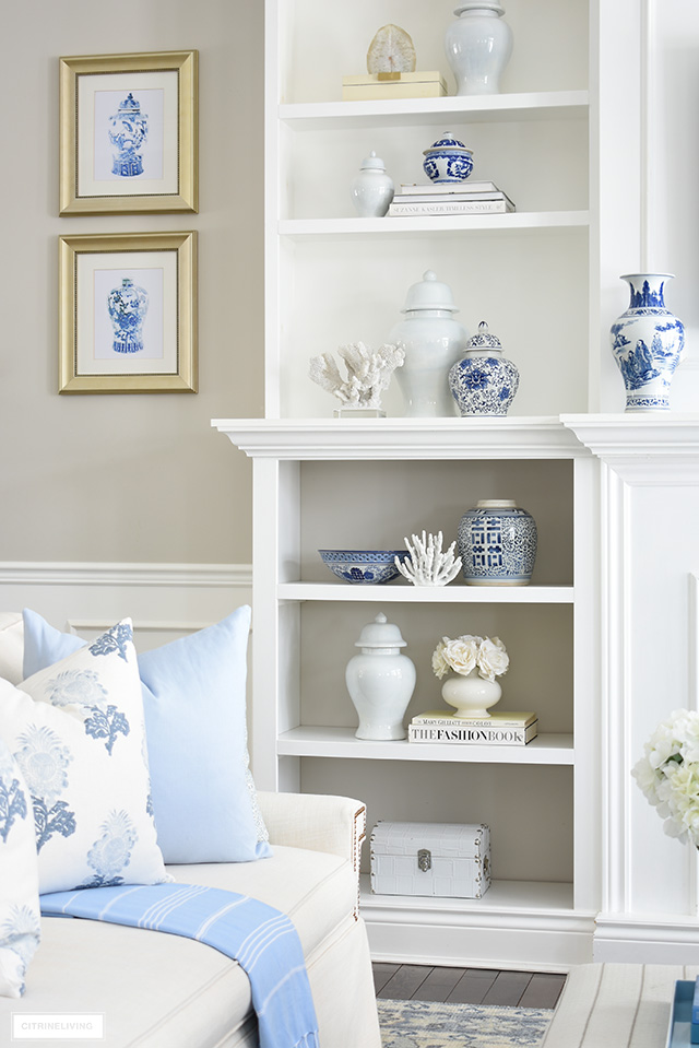 Gorgeous spring living room decorated with bookshelves styled in blue and white ginger jars and coastal accents.