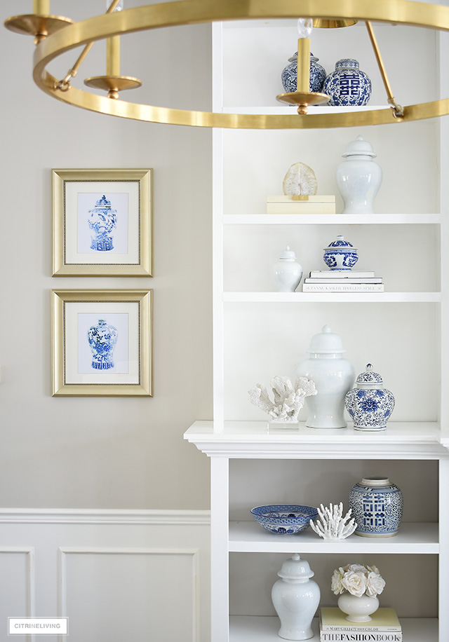 Beautiful chinoiserie ginger jar art prints hang next to blue and white styled bookshelves.