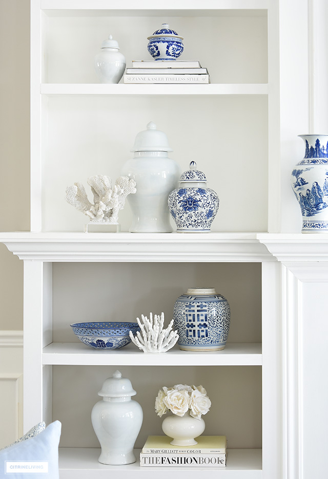 Spring living room decor with bookshelves styled in blue and white chinoiserie accents and ginger jars, design books, coral sculptures.