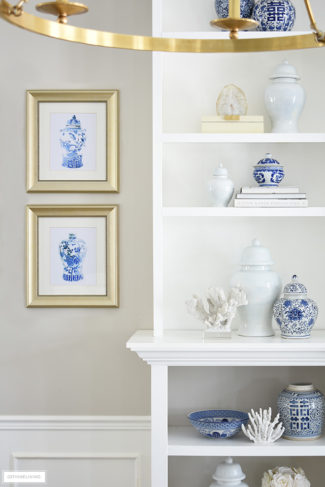 Spring living room decor with blue and white ginger jar art prints and bookshelf styling.