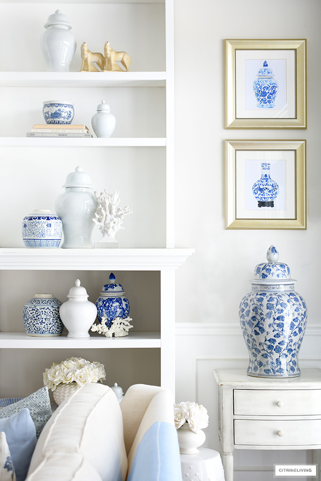 Spring living room decor with styled bookshelves in blue and white chinoiserie and coral sculptures.