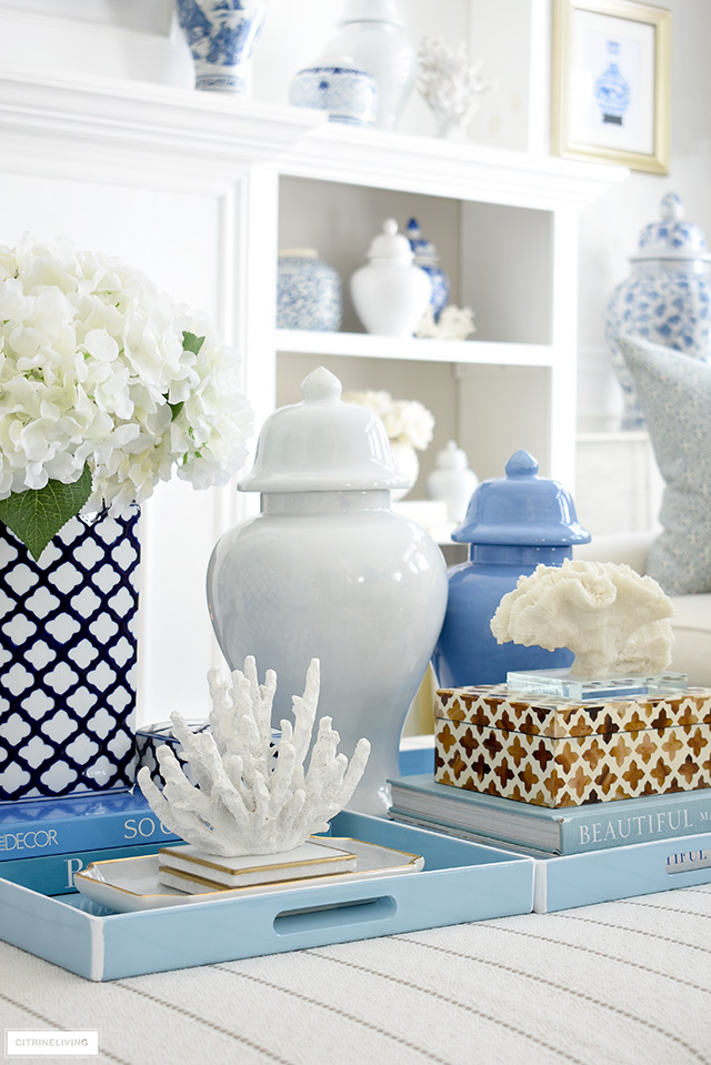 Styled light blue trays with ginger jars, decorative boxes, faux florals and coral sculptures.