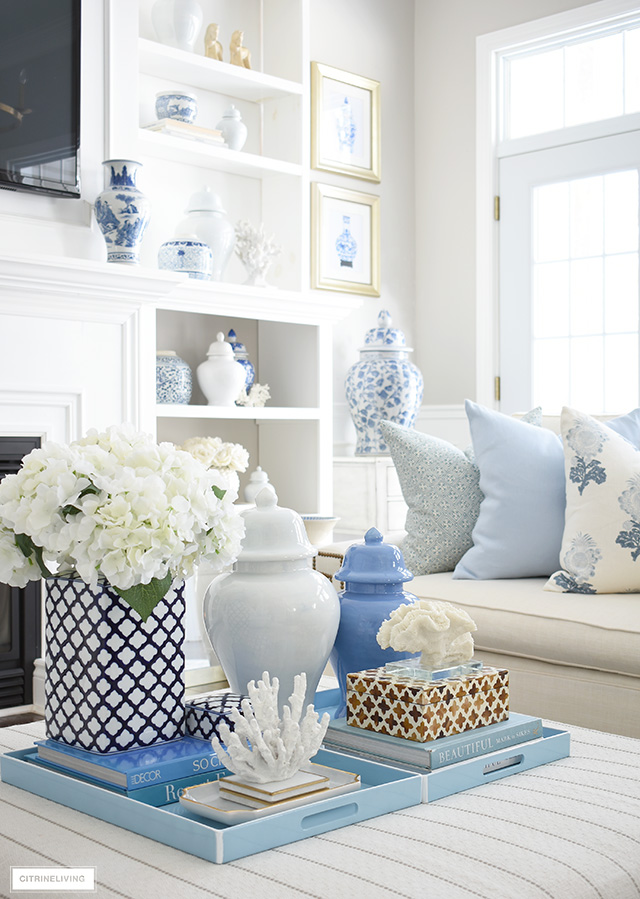 Coffee table styled with light blue trays, decorating books, decorative boxes, ginger jars and coral sculptures.