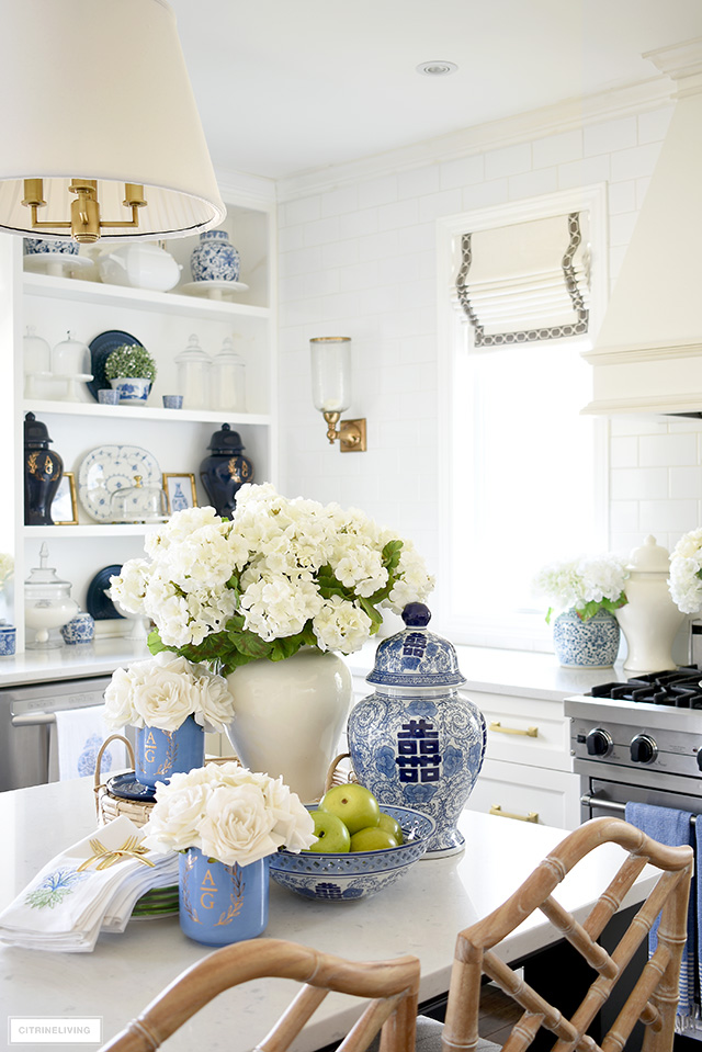 Kitchen decorated for spring with gorgeous blue and white accents, blue vases, faux flowers, pretty dishes and green apples.