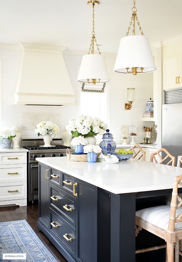 Kitchen island styled for spring with beautiful blue and white and faux flowers.