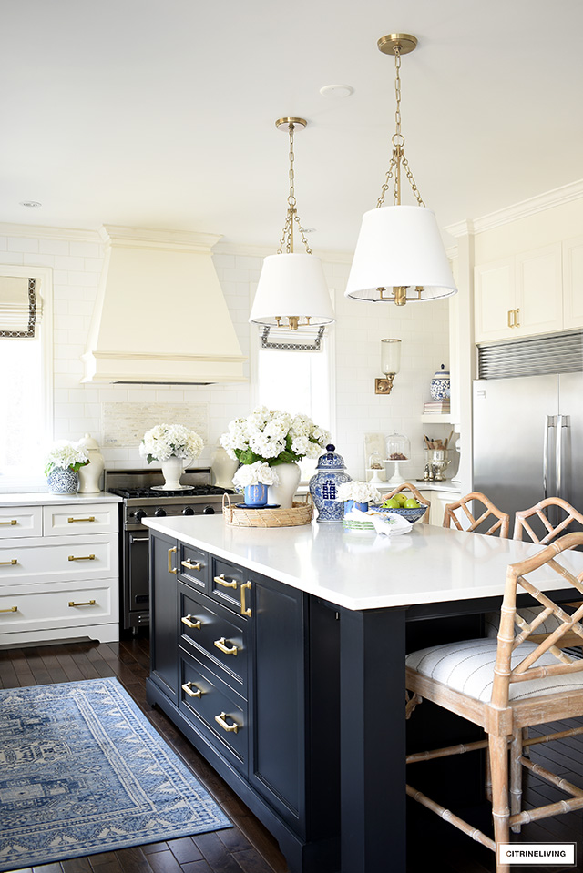 Kitchen island styled for spring with blue and white chinoiserie and faux flowers.