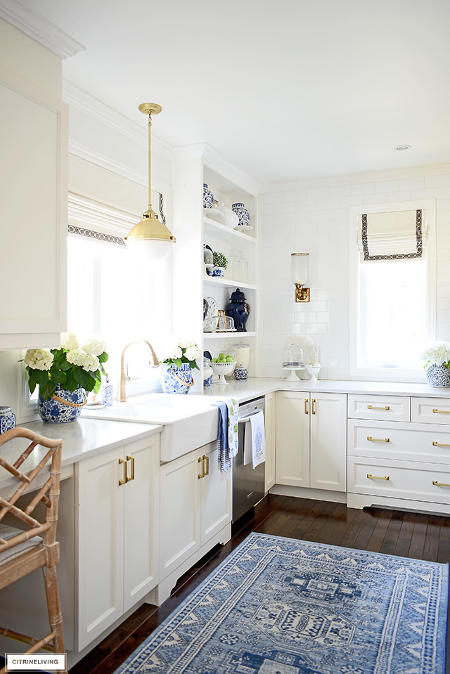 Spring kitchen decorating with blue rug, blue and white accents, faux flowers and green touches.