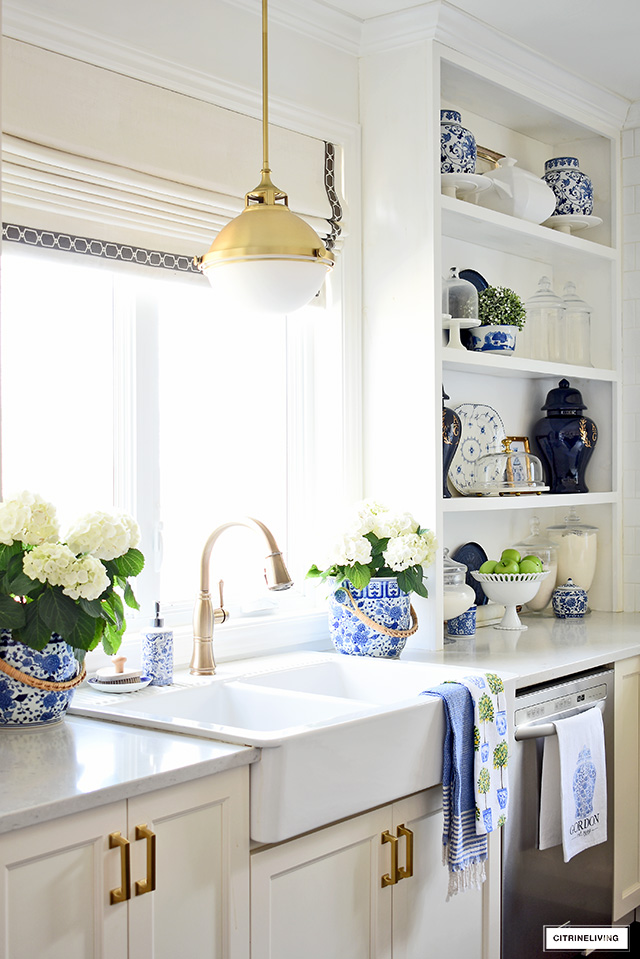 Kitchen farm sink decorated with blue and white chinoiserie champagne buckets and hydrangeas.