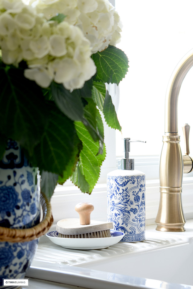 Kitchen sink styled with blue and white kitchen soap dispenser.