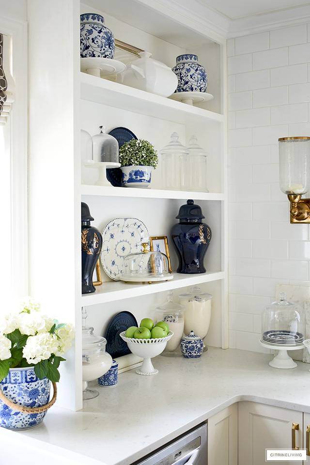 Open kitchen shelves decorated for spring with blue and white chinoiserie accents, glass apothecary jars and touches of greenery.