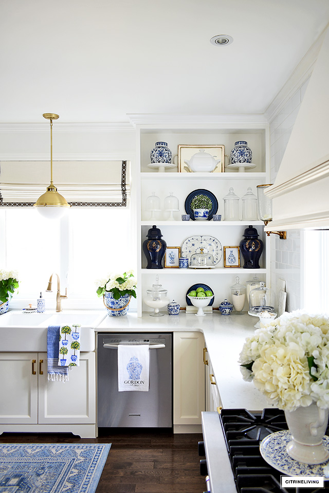 Open kitchen shelves decorated for spring with ginger jars, blue and white accents and greenery.