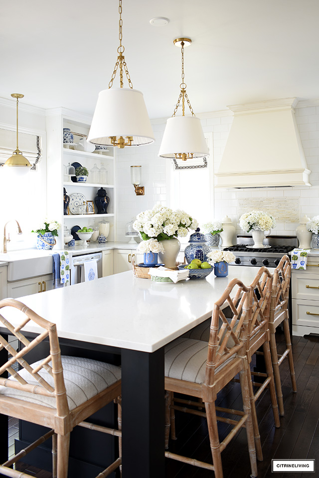 Kitchen styled for spring with blue and white accents, Chinese chippendale barstools and faux florals.