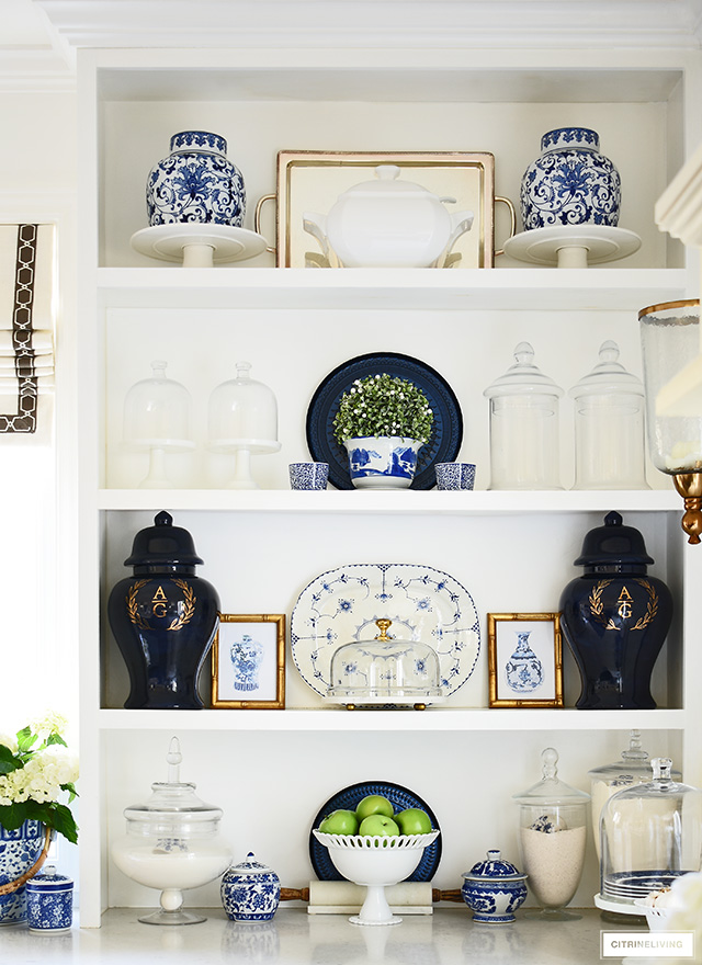 Kitchen shelves decorated for spring with blue and white chinoiserie accents, monogrammed ginger jars and green touches.