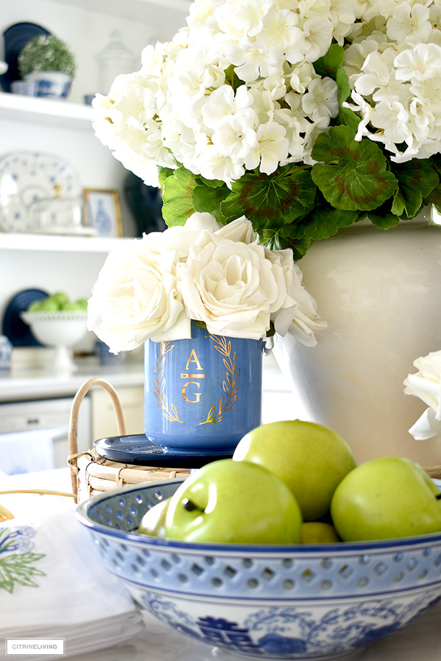 Beautiful spring kitchen vignette with monogrammed vase, faux florals, blue and white chinoiserie bowl and green apples.