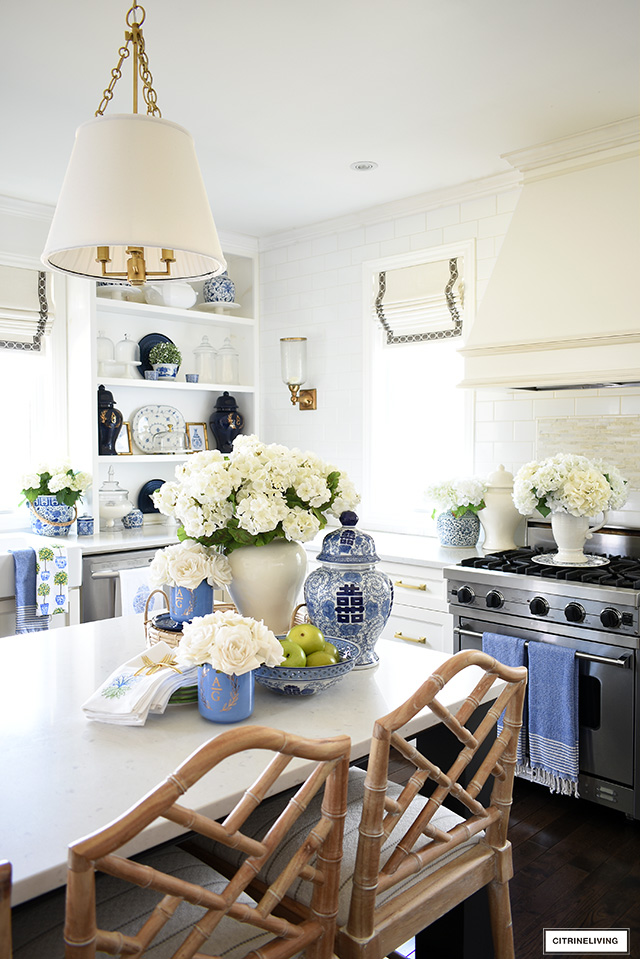 Kitchen decorated for spring with gorgeous blue and white accents and faux flowers.