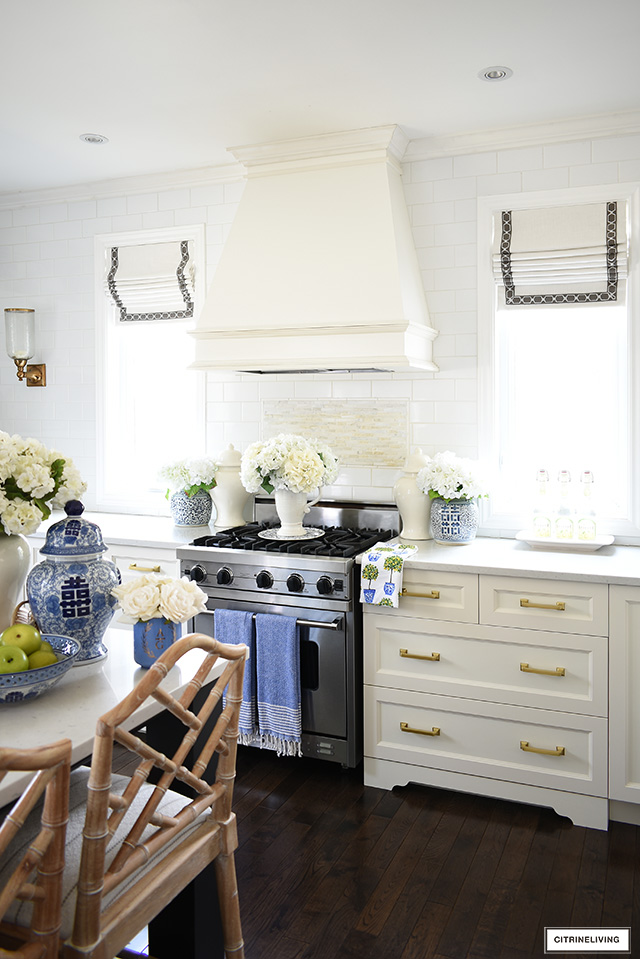 Kitchen styled for spring with blue and white chinoiserie jars, green accents and faux flowers.