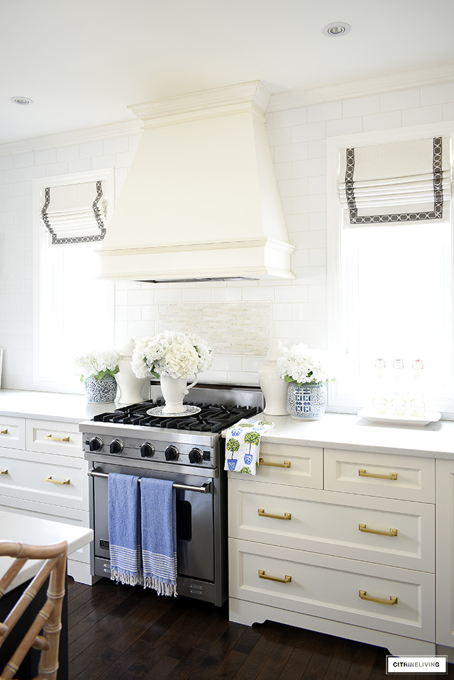 Kitchen range hood decorated for spring with blue and white ginger jars and faux flowers.