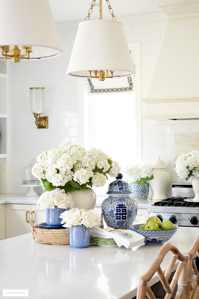 Kitchen decorated for spring with gorgeous blue and white accents, faux flowers, pretty dishes and green apples.