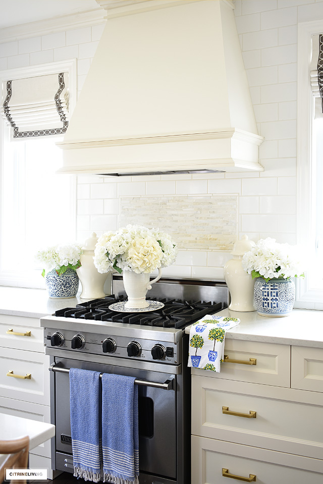 Kitchen range hood styled for spring with pretty ginger jars and faux florals.