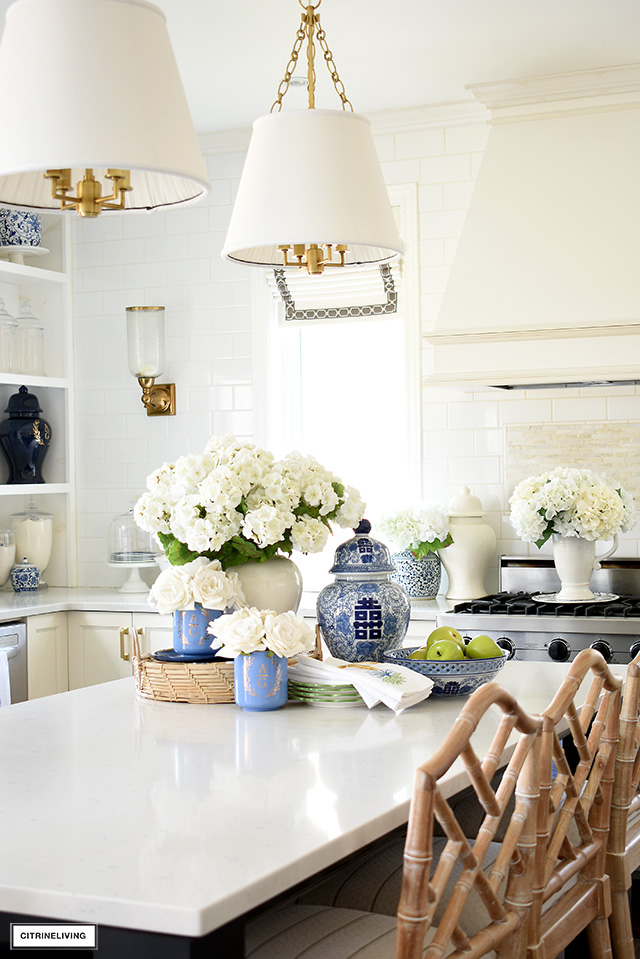 Beautiful kitchen styled for spring with faux florals, blue and white chinoiserie, and green accents.