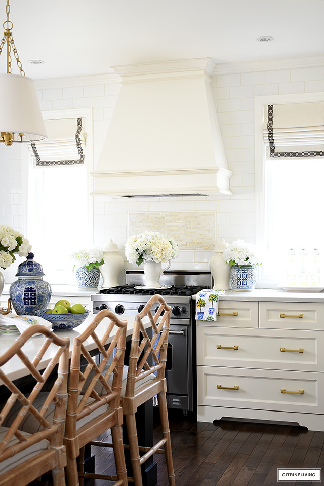Spring kitchen decorating - range hood styled with ginger jars and faux flowers on each side is a beautiful focal point.