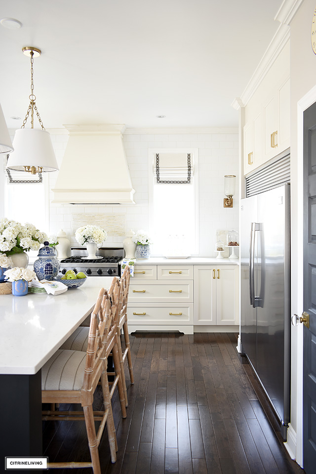 Kitchen decorated for spring with faux flowers and blue and white accents.