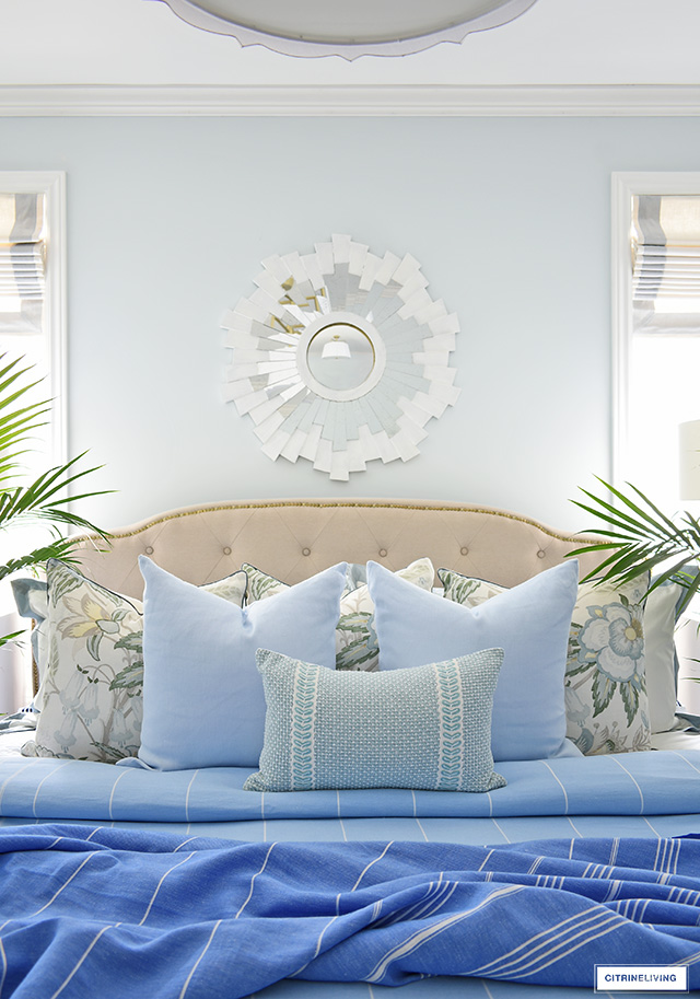 Gorgeous summer bedding with layers of striped throws and elegant pillows in light blues and soft greens.