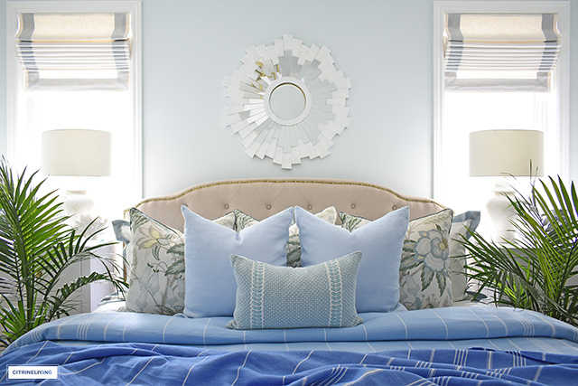 Gorgeous summer bedding with layers of striped throws and elegant pillows in light blues and soft greens is fresh and breezy for warmth weather months!
