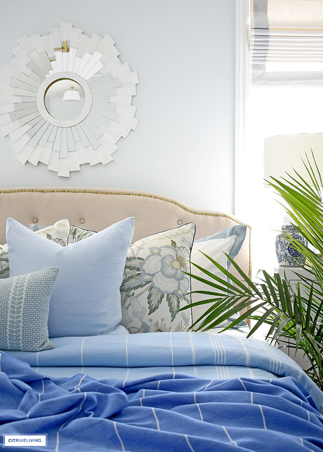 Beautiful summer bedding layered with blue throws and pillows.