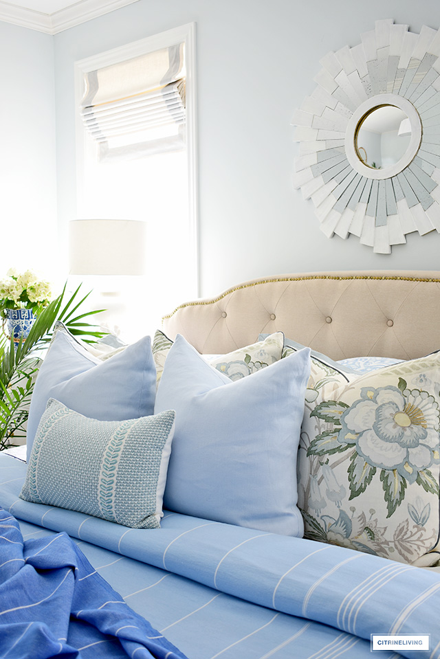 Blue and white fresh summer bedroom decorating with palms, hydrangeas, pretty throw blankets and goregous pillows.