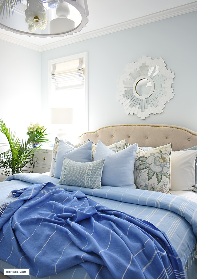 Summer bedroom decorating with layers of pillows and throw blankets in blues and greens.