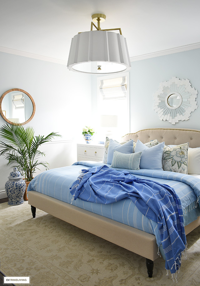 Gorgeous summer bedroom decorating with palms, striped accent throws and beautifully layered pillows.