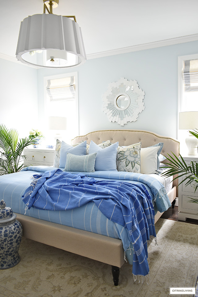 Beautiful and breezy summer bedroom decorating with layers of blues and greens, palm plants chinoiserie touches.