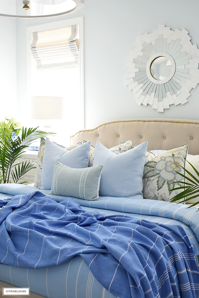 Designer throw pillows layered in soft blues and light greens is a fresh and airy look for summer.