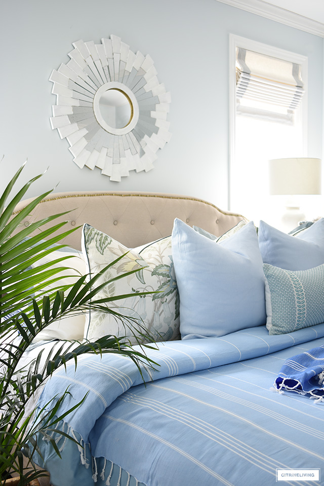 Layered throw pillows in blues and greens creates a beautiful and breezy summer bedroom look!