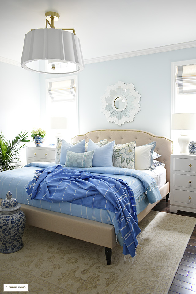 Gorgeous summer bedroom decorating with layered blue blankets, chic throw pillows and palm plants.
