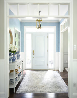 A gorgeous entryway decorated for summer featuring beautiful faux blue grasscloth wallpaper.