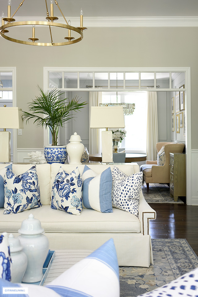 Living room sofa styled for summer with blue and white pillows.