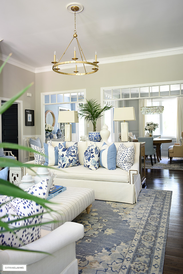 A gorgeous living room styled for summer with blue and white florals, stripes and animal print pillows.