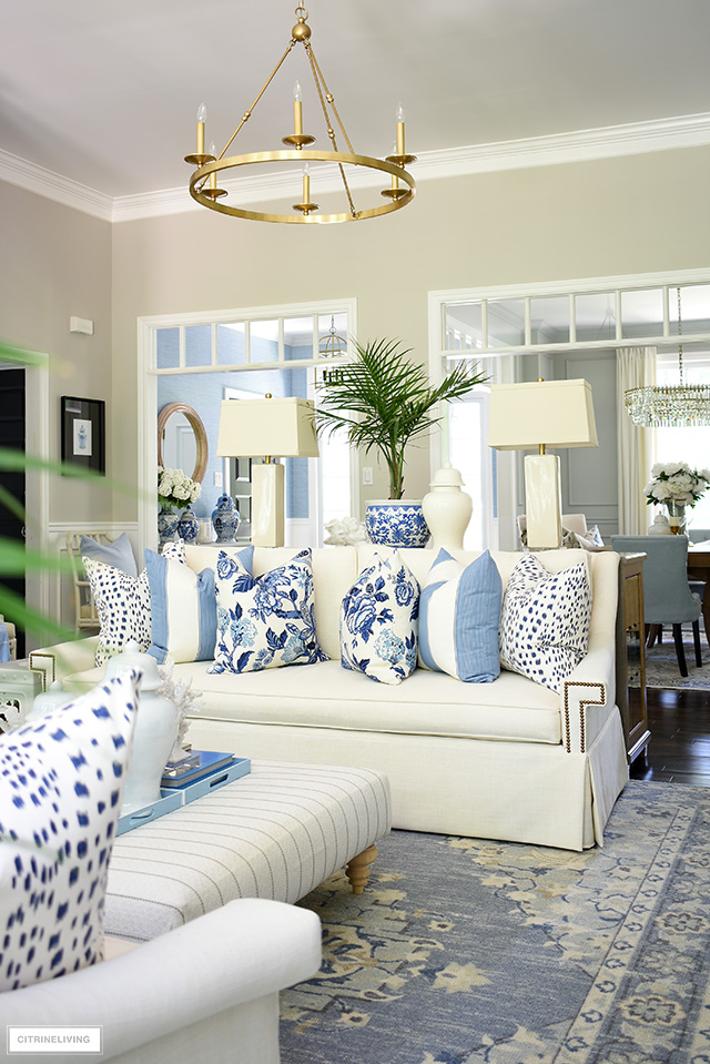 Living room decorated for summer with blue and white pillows and palm plants is an easy way to achieve a coastal look.