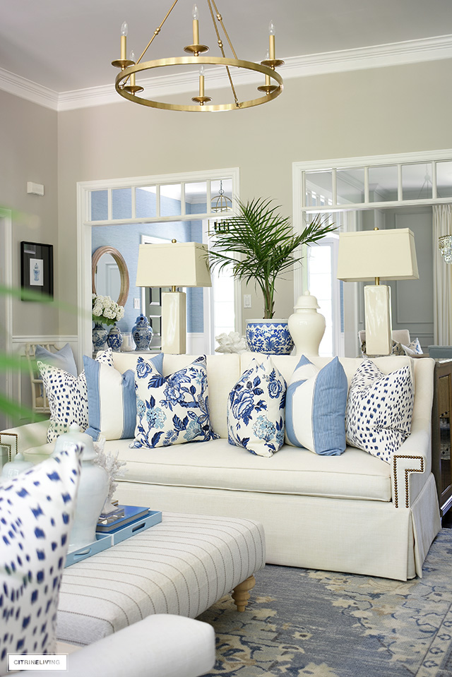 Summer living room decor with blue and white pillows, chinoiserie, coral, palms and ginger jars.