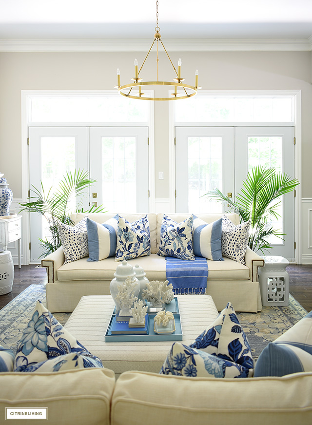 Summer living room decorated in blue and white accented with majesty palms.