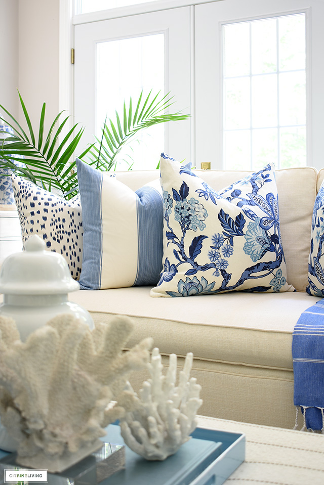 Hamptons syle pillows in blue and white styled on a tailored white sofa.