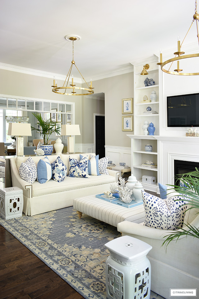 Living room decorated for summer with blue and white decor and palms is breezy and beautiful.