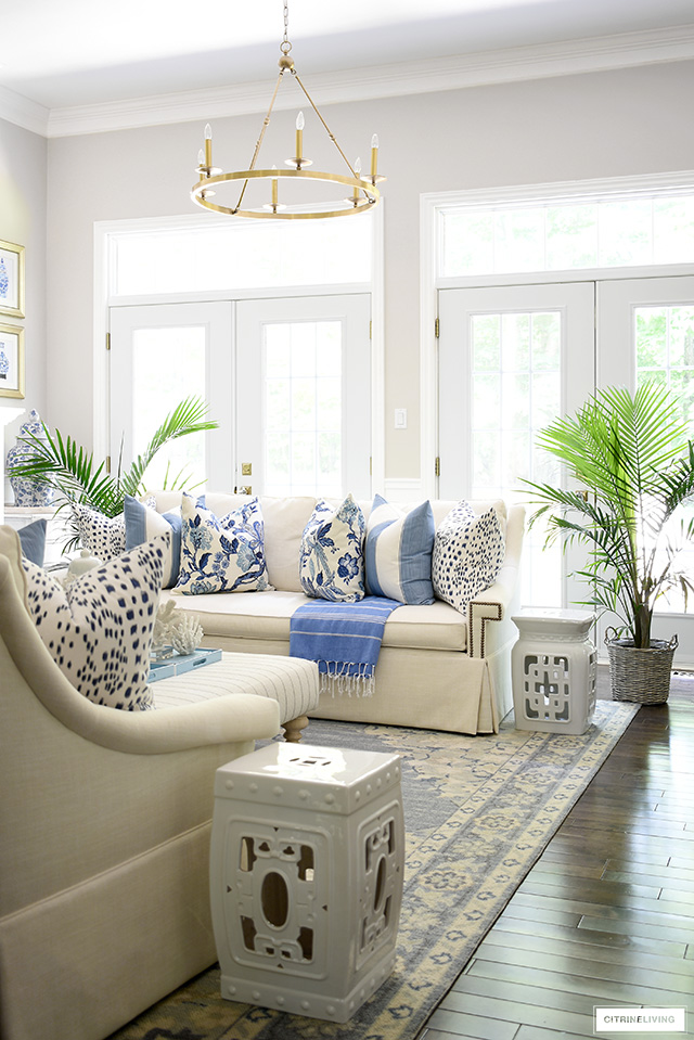 Summer living room decor with blue and white pillows, rug and palm plants.