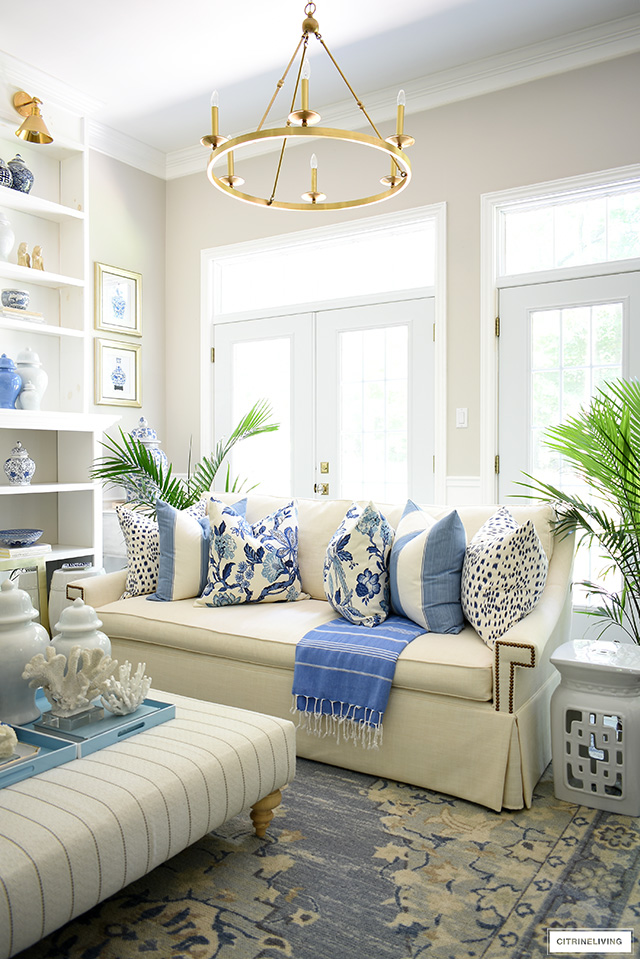 A collection of hamptons-inspired blue and white print pillows styled on a white sofa for summer.