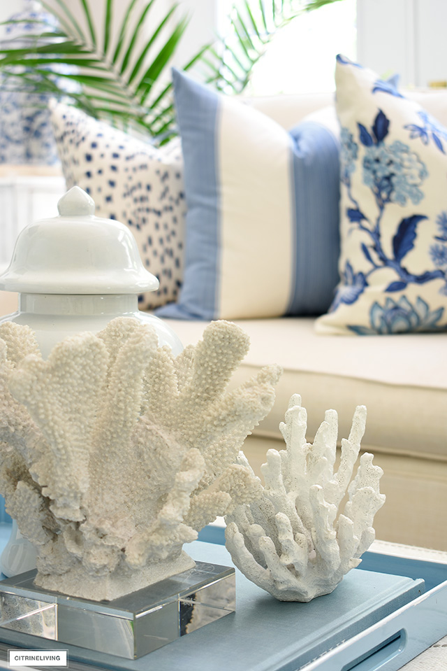 Coral sculptures styled for summer on a light blue tray.